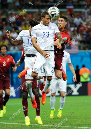 United States' Fabian Johnson (23) heads the ball away from Portugal's Cristiano Ronaldo, right, during the group G World Cup soccer match between the USA and Portugal at the Arena da Amazonia in Manaus, Brazil