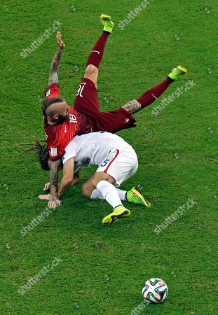 Portugal's Raul Meireles falls over United States' Matt Besler, bottom, during the group G World Cup soccer match between the USA and Portugal at the Arena da Amazonia in Manaus, Brazil