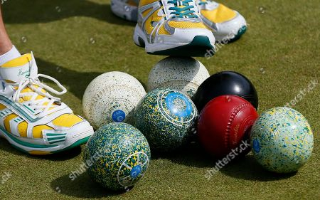 Stock Image of Australia's David Peacock collects the bowls with his feet as his team play India for the bronze medal bowls in the Lawn Bowls competition at the Commonwealth Games Glasgow 2014, in Glasgow, Scotland, Friday, Aug., 1, 2014. Australia won the bronze medal