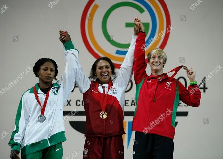 Gold medalist Zoe Smith of England, centre, lifts her hands with didi Winifred of Nigeria, left, silver medal and Michaela Breeze of Wales bronze medal during the medal ceremony for the women's 58 kg weightlifting competition the Commonwealth Games Glasgow 2014, in Glasgow, Scotland, Saturday, July, 26, 2014