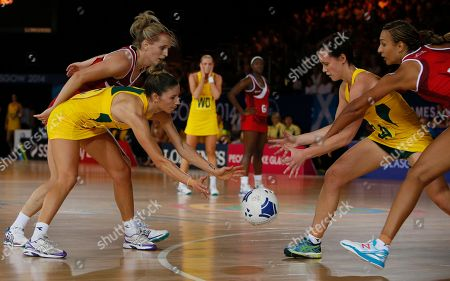 Stock Photo of Australia's Kimberley Ravillion, left front, passes the ball to teammate Natalie Medhurst, second right under pressure from Sara Bayman, top left and Geve Mentor of England during a preliminary round netball match at the Commonwealth Games Glasgow 2014, in Glasgow, Scotland, Saturday, July, 26, 2014. Australia won the game 49-48