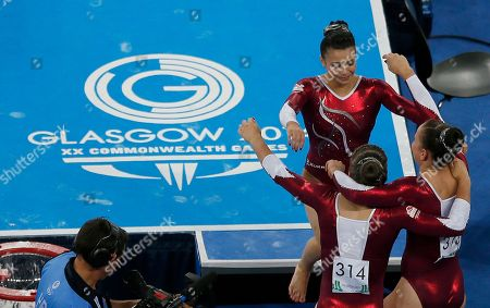 Claudia Fragapane of England, top walks into the arms of her teammates Ruby Harrold, left, and Hannah Whelan, right, after her floor routine at the women's individual all-round gymnastic competition at the Commonwealth Games Glasgow 2014, in Glasgow, Scotland, Wednesday, July, 30, 2014