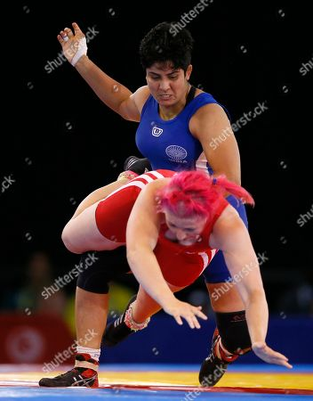 Geetika Jakhar, at rear, of India pushes over Sarah Connolly of Wales during their women's freestyle 63 kg wrestling bout at the Commonwealth Games Glasgow 2014, in Glasgow, Scotland, Thursday, July, 31, 2014