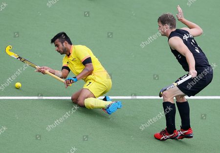 Manpreet Singh of India, left, vies for the ball with Steve Edwards of New Zealand in their men's semifinal hockey match during the Commonwealth Games 2014 in Glasgow, Scotland