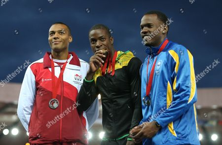 Andrew Riley, centre, of Jamaica winner of the gold medal for the men's 110 meter hurdles bits his medal as he poses for photographs with William Sharman, left, silver medal and Shane Brathwaite, of Barbados bronze medal following the medal ceremony for the event in Hampden Park at the Commonwealth Games Glasgow 2014, in Glasgow, Scotland