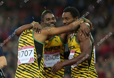 Rasheed Dwyer, right of Jamaica, celebrates after he lead home a Jamaica 1, 2, 3, with Warren Weir, left, who placed second and Jason Livermore who place 3rd in the men's 200 meter race at Hampden Park Stadium during the Commonwealth Games 2014 in Glasgow, Scotland, . Dwyer won the gold medal winning the race