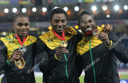 Rasheed Dwyer, centre holds up his gold medal with Warren Weir, left, silver medal and Jason Livermore bronze medal following the medal ceremony for the men's 200 meter race as Jamaica had a 1,2,3 in the race, at Hampden Park Stadium during the Commonwealth Games 2014 in Glasgow, Scotland, . Dwyer won the gold medal winning the race