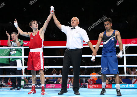 Michael Conlan, left, of Northern Ireland reacts as the referees award him the bout and the gold medal defeating Qais Ashfaq of England in their men's gold medal bantamweight boxing bout at the Commonwealth Games Glasgow 2014, in Glasgow, Scotland, Saturday, Aug., 2, 2014