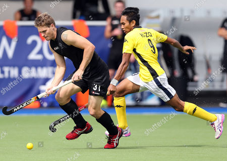 New Zealand's Steve Edwards, left, vies for the ball with Malaysia's Muhammad Haziq Samsul, right, during the men's field hockey match at the Commonwealth Games Glasgow 2014, at the National Hockey Centre, Glasgow, Scotland