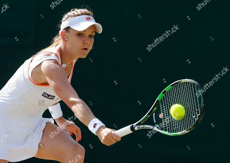 Agnieszka Radwanska of Poland plays a return to Michelle Larcher De Brito of Portugal during their women's singles match at the All England Lawn Tennis Championships in Wimbledon, London