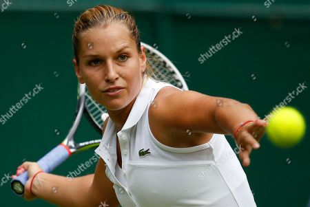 Domimika Cibulkova of Slovakia plays a return to Aleksandra Wozniak of Canada during their first round match at the All England Lawn Tennis Championships in Wimbledon, London