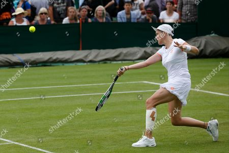 Romina Oprandi of Switzerland returns to Mona Barthel of Germany during their first round match at the All England Lawn Tennis Championships in Wimbledon, London