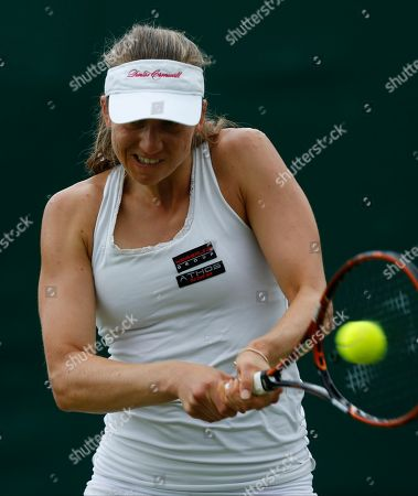 Mona Barthel of Germany plays a return to Romina Oprandi of Switzerland during their first round match at the All England Lawn Tennis Championships in Wimbledon, London