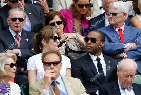 Canada's High Commissioner to London Gordon Campbell, top right, and former International Olympic Committee President Jacques Rogge, top left, sit in the Royal Box on centre court with British actor Chiwetel Ejiofor, center right, and Sari Mercer, center left, prior to the women's singles final between Eugenie Bouchard of Canada and Petra Kvitova of the Czech Republic at the All England Lawn Tennis Championships in Wimbledon, London