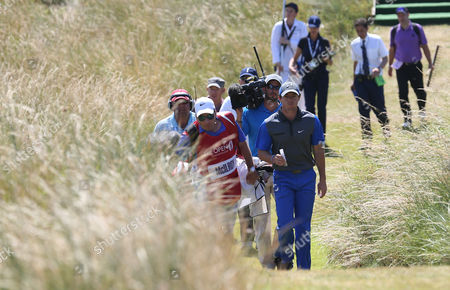 Rory McIlroy of Northern Ireland walks up to the 14th tee box with his caddie JP Fitzgerald during the first day of the British Open Golf championship at the Royal Liverpool golf club, Hoylake, England
