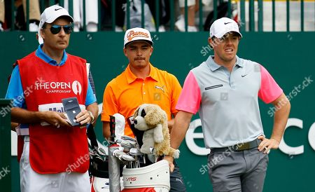 Rickie Fowler of the US, center, Rory McIlroy of Northern Ireland, right, and his caddie JP Fitzgerald wait to tee off the 1st during the final round of the British Open Golf championship at the Royal Liverpool golf club, Hoylake, England