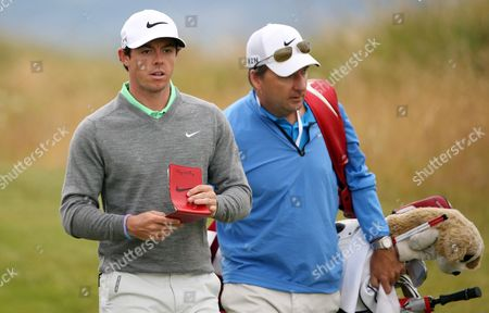 Rory McIlroy of Northern Ireland walks along the 4th fairway with his caddie JP Fitzgerald, right, during a practice round ahead of the British Open Golf championship at the Royal Liverpool golf club, Hoylake, England, . The British Open Golf championship starts Thursday July 17