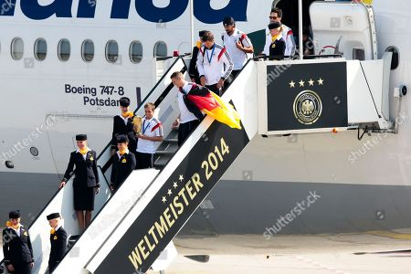 "The players of German national soccer team Philipp Lahm, Sebastian Schweinsteiger, Thomas Mueller, Sami Khedira and Mats Hummels from left, arrive at Tegel airport in Berlin . G Germany's World Cup-winning team has returned home from Brazil to celebrate the country's fourth title with huge crowds of fans. The team's Boeing 747 touched down at Berlin's Tegel airport midmorning Tuesday after flying a lap of honor over the ""fan mile"" in front of the landmark Brandenburg Gate. Words read World Champion 2014"