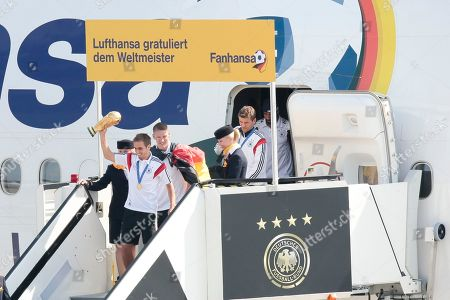 "The players of German national soccer team, Philipp Lahm with trophy, Sebastian Schweinsteiger, Thomas Mueller and Sami Khedira, from left arrive at Tegel airport in Berlin . Germany's World Cup-winning team has returned home from Brazil to celebrate the country's fourth title with huge crowds of fans. The team's Boeing 747 touched down at Berlin's Tegel airport midmorning Tuesday after flying a lap of honor over the ""fan mile"" in front of the landmark Brandenburg Gate. Words read Lufthansa congratulates the World Champion, Fanhansa"