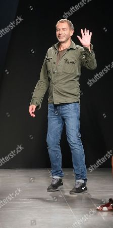 German designer Tomas Maier acknowledges applause following the presentation of the Bottega Veneta men's Spring-Summer 2015 collection, part of the Milan Fashion Week, unveiled in Milan, Italy