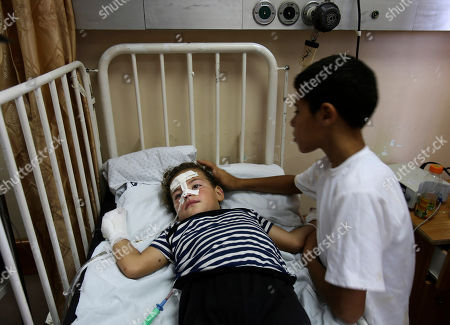 Ayman al Danaf, 13, tries to comfort his 5-year-old wounded sister, Amal, as she receives treatment at a hospital in Gaza City, in the northern Gaza Strip, . A rocket fired by Palestinian militants toward Israel exploded in the northern Gaza Strip early Wednesday, killing a 3-year-old girl and wounding three other people, a medical official said. Ashraf al-Kidra said it was not clear whether the rocket was misfired, or whether an Israeli rocket-defense system intercepted it and caused it to explode over Palestinian territory