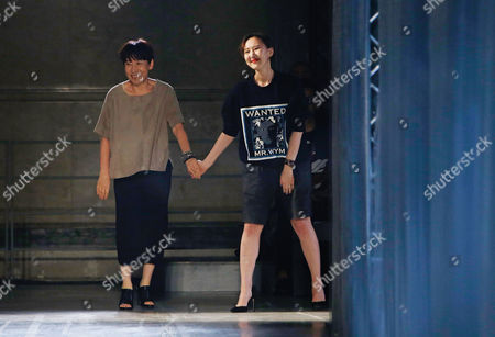 Wooyoungmi, Katie Chung South Korean fashion designer Wooyoungmi, left, and her daughter and fellow creative director, Katie Chung, acknowledge applause at the end of their men's spring-summer 2015 fashion collection presented in Paris, France