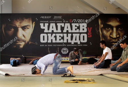 "Chechens pray in front of poster of Uzbekistan's ""White Tyson"" Ruslan Chagaev and American Fres Oquendo during their WBA heavyweight boxing championship fight at Ahmat Arena, in Grozny, Russia, . Former WBA heavyweight champion Chagaev became a two-time champ, as he won a 12-round majority verdict over Oquendo to pick up the ""regular"" WBA strap"