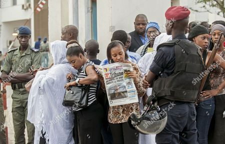 Stock Picture of Supporters of Karim Wade, the son of former Senegal president Abdoulaye Wade, stand among Senegal Police, foreground, as they await his arrival at court, in the city of Dakar, Senegal, . The son of Senegal's president is going on trial after more than a year in jail, accused of illegally amassing some $248 million. Karim Wade served as a government minister during his father's tenure and prosecutors have charged him with illicit enrichment