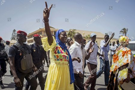 A supporter of Karim Wade, the son of former Senegal president Abdoulaye Wade, gestures as she and others are followed by Senegal Police, left, upon arrival at court, in the city of Dakar, Senegal, . The son of Senegal's president is going on trial after more than a year in jail, accused of illegally amassing some $248 million. Karim Wade served as a government minister during his father's tenure and prosecutors have charged him with illicit enrichment