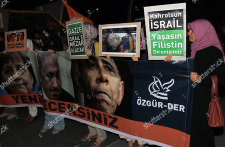 """Pro-Palestinian Turks stage a protest rally against Israel's ground operation in Gaza Strip, outside the US embassy in Ankara, Turkey, late . Turkish Prime Minister Recep Tayyip has intensified Saturday his fiery rhetoric against Israel over its ground invasion of Gaza, accusing the country of """"state terrorism"""" and """"genocide."""" The banner with images of US President Barack Obama, Israeli Prime Minister Binyamin Netanyahu and German Chancellor Angela Merkel reads: """" You will be defeated."""" Placard to the left reads """" They are racing towards savagery!"""", and placard at centre """" Palestine will be Israel's grave"""