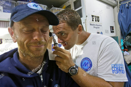Ryan Stancil, Matt Ferraro Matt Ferraro, left, director of photography, cameraman for Mission 31, is examined by mission doctor Ryan Stancil inside Aquarius Reef Base, a laboratory 63 feet below the surface in the waters off Key Largo, in the Florida Keys National Marine Sanctuary, . A team of filmmakers and researchers dove with Fabien Cousteau on June 1 to Aquarius. At the mission's mid-point, the FIU researchers traded places with researchers from Northeastern, who will return to land July 2 with Cousteau. They've been studying the effects of climate change and pollutants such as fertilizers on the reef