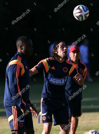 Radamel Falcao, Eder Alvarez Balanta Colombia's Radamel Falcao, right, eyes the ball as teammate Eder Alvarez Balanta stands by during their training session in Buenos Aires, Argentina, . Colombia's national soccer team is hoping Falcao will be able to play at the World Cup after his knee injury. Brazil is hosting the international soccer tournament starting in June