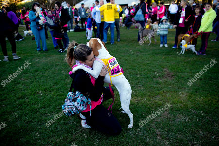 Stock Photo of Lala embraces her owner Luciana Vazquez before competing in the 5th edition of the annual Argentina dog run in Buenos Aires, Argentina, .The race is divided into different categories, according to distance, 1K for children with their families, 3k and 5K