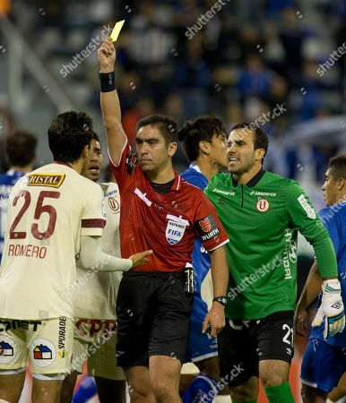 Carlos Ulloa, Angel Romero, Jose Carvallo Referee Carlos Ulloa, from Chile, shows a yellow card for Angel Romero of Peru's Universitario, left, as goalkeeper of Peru's Universitario Jose Carvallo, right, complains during a Copa Libertadores soccer match with Argentina's Velez Sarsfield in Buenos Aires, Argentina