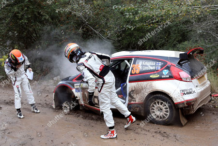 Jari Ketomaa, Kaj Lindstrom Driver Jari Ketomaa, right, and his co-driver Kaj Lindstrom, left, both from Finland, check out their Ford Fiesta, damaged aafter blowing a tire during stage 3 of the first day of the FIA WRC Argentina Rally in Agua de Oro, Cordoba province, Argentina