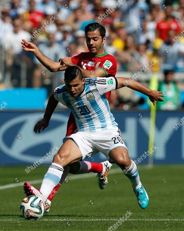Argentina's Sergio Aguero tries the shield the ball from Iran's Pejman Montazeri during the group F World Cup soccer match between Argentina and Iran at the Mineirao Stadium in Belo Horizonte, Brazil