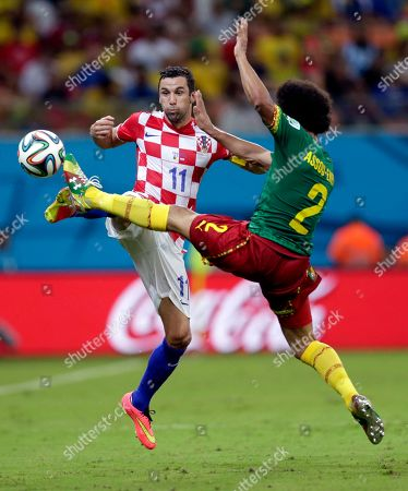 Croatia's Darijo Srna, left, and Cameroon's Benoit Assou-Ekotto battle for the ball during the group A World Cup soccer match between Cameroon and Croatia at the Arena da Amazonia in Manaus, Brazil