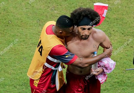 Cameroon's Benoit Assou-Ekotto, right, is comforted after losing 0-4 to Croatia during the group A World Cup soccer match between Cameroon and Croatia at the Arena da Amazonia in Manaus, Brazil