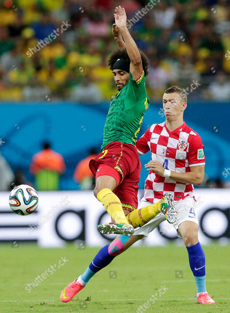 Cameroon's Benoit Assou-Ekotto, left, kicks the ball away from Croatia's Ivan Perisic during the group A World Cup soccer match between Cameroon and Croatia at the Arena da Amazonia in Manaus, Brazil