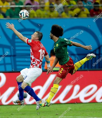 Croatia's Ivica Olic, left, and Cameroon's Benoit Assou-Ekotto challenge for the ball during the group A World Cup soccer match between Cameroon and Croatia at the Arena da Amazonia in Manaus, Brazil
