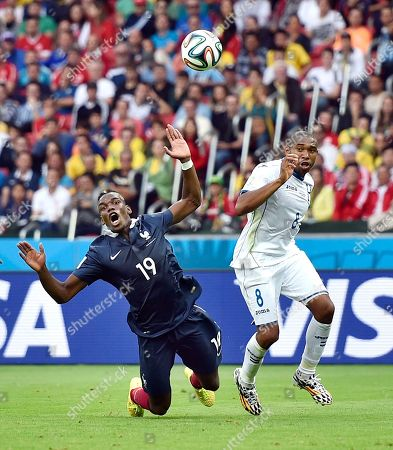 France's Paul Pogba falls after being run into by Honduras' Wilson Palacios during the group E World Cup soccer match between France and Honduras at the Estadio Beira-Rio in Porto Alegre, Brazil, . Palacios was booked for the second time and ejected from the match