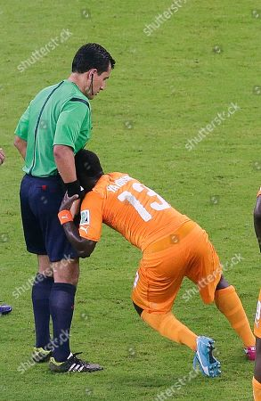 Stock Photo of Referee Enrique Osses from Chile helps up Ivory Coast's Didier Ya Konan, right, during the group C World Cup soccer match between Ivory Coast and Japan at the Arena Pernambuco in Recife, Brazil, . Ivory Coast won 2-1