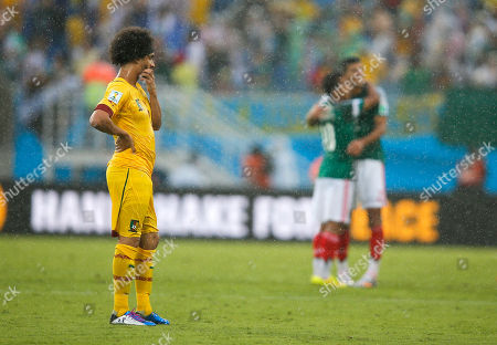 Cameroon's Benoit Assou-Ekotto, left, watches as Mexico's players celebrate following their 1-0 win during the group A World Cup soccer match between Mexico and Cameroon in the Arena das Dunas in Natal, Brazil