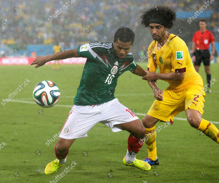 Cameroon's Benoit Assou-Ekotto (2) tries to pull Mexico's Giovani dos Santos (10) away from the ball during the second half of the group A World Cup soccer match between Mexico and Cameroon in the Arena das Dunas in Natal, Brazil