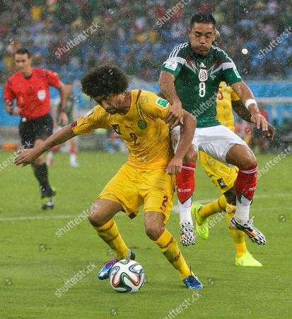 Mexico's Marco Fabian (8) attempts to pull Cameroon's Benoit Assou-Ekotto (2) from the ball during the second half of the group A World Cup soccer match between Mexico and Cameroon in the Arena das Dunas in Natal, Brazil