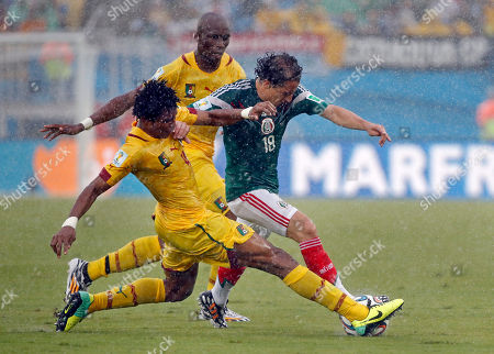 Mexico's Andres Guardado, right, is challenged by Cameroon's Jean Makoun during the group A World Cup soccer match between Mexico and Cameroon in the Arena das Dunas in Natal, Brazil