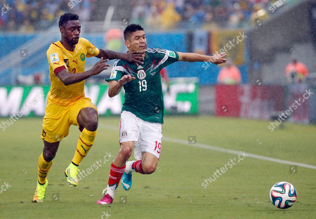 Cameroon's Benoit Assou-Ekotto, left, and Mexico's Oribe Peralta fight for the ball during the group A World Cup soccer match between Mexico and Cameroon in the Arena das Dunas in Natal, Brazil