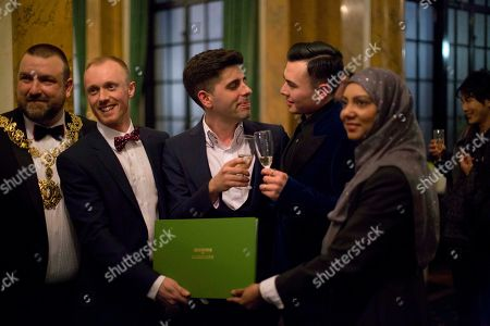 Sean Adl-Tabatabai, third from left, and Sinclair Treadway, fourth from left, pose for photographs with, from left, the openly gay mayor of Camden Jonathan Simpson, deputy superintendent registrar Steven Lord and registrar officer Tania Uddin, after they were announced officially married in a wedding ceremony in the Council Chamber at Camden Town Hall in London, . Gay couples in Britain waited decades for the right to get married. When the opportunity came, some had just days to plan the biggest moment of their lives. Adl-Tabatabai, a 32-year-old TV producer from London, and Treadway, a 20-year-old student originally from Los Angeles, registered their intent to marry on March 13, the first day gay couples could sign up for wedding ceremonies under Britain's new law. Eager to be part of history, the two men picked the earliest possible moment - just after midnight Friday, when the act legalizing same-sex marriage takes effect