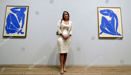 Sophie Matisse, the great-granddaughter of Henri Matisse, poses alongside his work 'Blue Nude III 1952', left, and Blue Nude II 1952', right, at The Tate Modern in London, . The artworks are part of the 'Henri Matisse: The Cut-Outs' exhibition that runs at the gallery from April 17 until Sept. 7, 2014