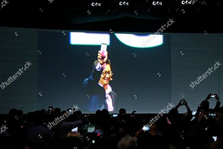 Members of the media take pictures as Dr. Ramchan Woo, Head of Smartphone Planning for LG, is seen on a screen as he unveils the company's new smartphone called the G3 at a press event in London